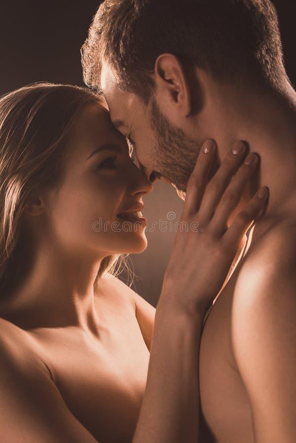счастливые нагие любовники усмехаясь и обнимая, стоковая фотография