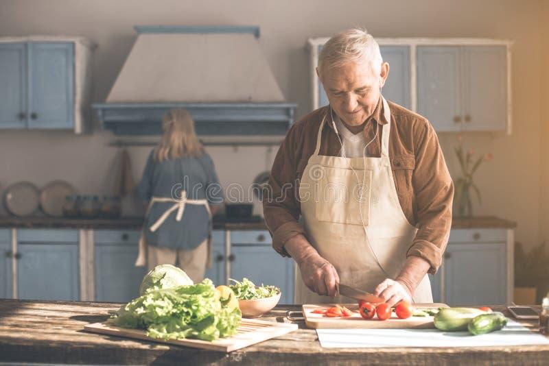 Счастливые овощи вырезывания старшего человека приближают к женщине в кухне стоковые фото