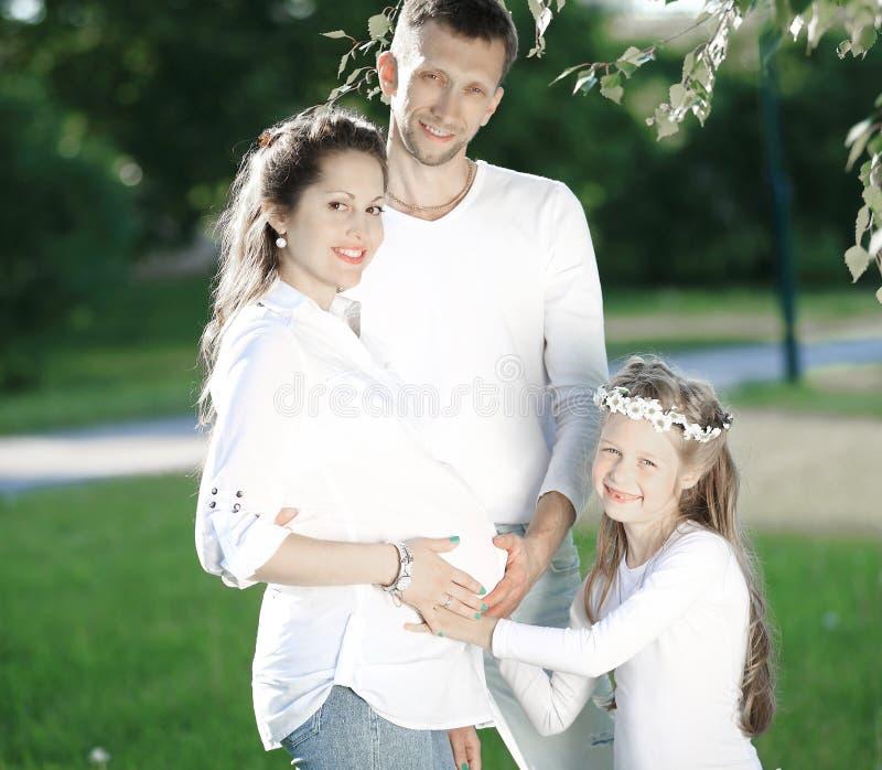 Счастливые отец и дочь семьи, и беременная мама в парке стоковое изображение rf