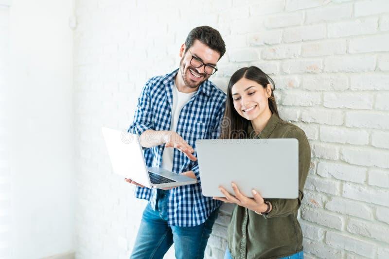 Счастливые партнеры с технологиями в рабочем месте стоковое изображение