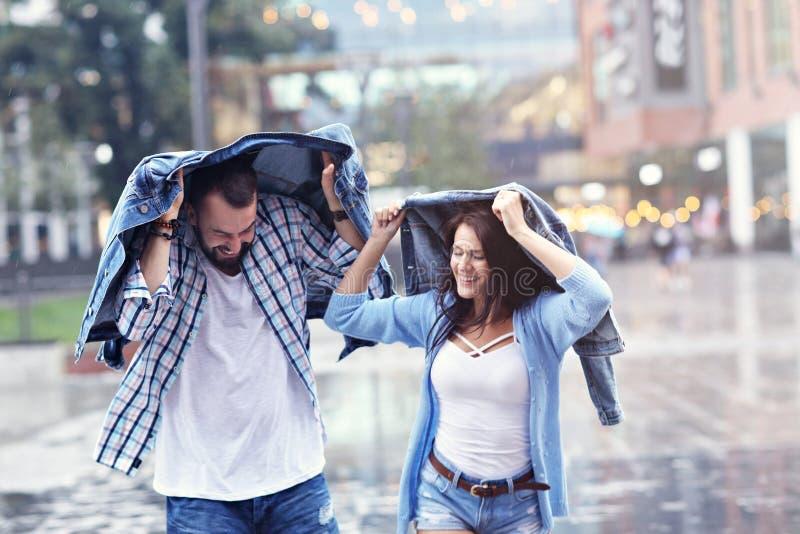 Счастливые пары бежать в дожде в городе стоковые изображения