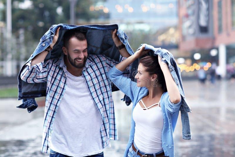 Счастливые пары бежать в дожде в городе стоковое фото