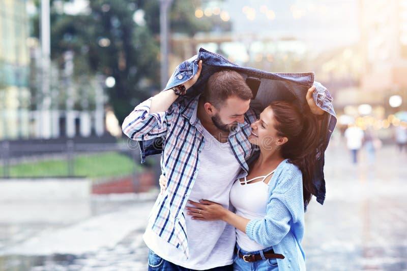 Счастливые пары бежать в дожде в городе стоковые фото
