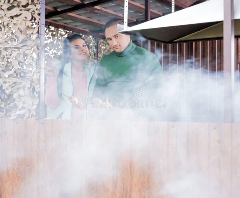 Счастливые пары варя shashlyk совместно осматривают стоковое изображение rf