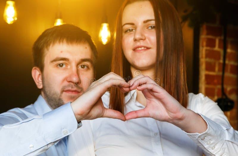 Счастливые пары в любов показывая сердце с пальцами в интерьере просторной квартиры, горящими светами на заднем плане стоковая фотография