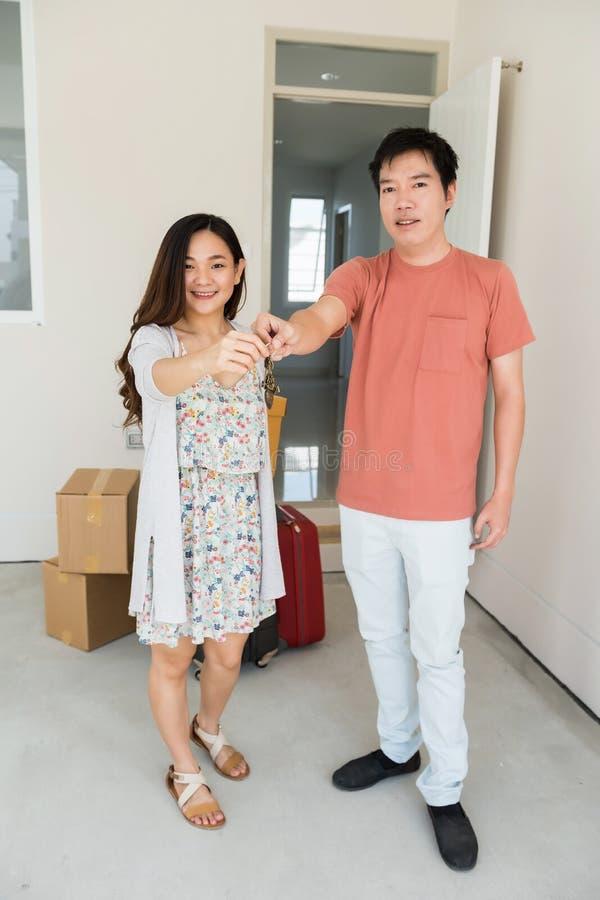 Счастливые пары держат ключ на двери нового дома стоковые фотографии rf