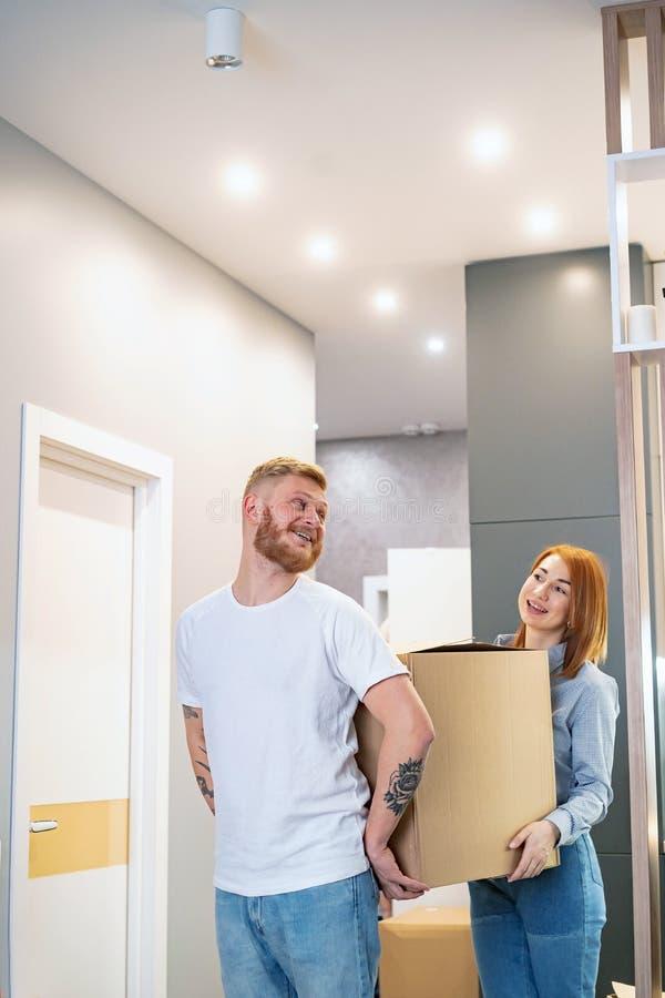 Счастливые пары держа картонные коробки и двигая к новому месту стоковое фото