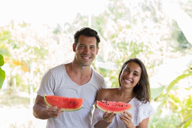 Счастливые пары держа кусок арбуза в руках жизнерадостное усмехаясь объятие человека и женщины с арбузом Outdoors стоковые изображения rf