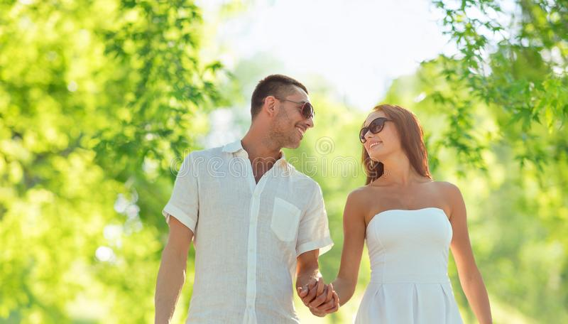 Счастливые пары держа руки над естественной предпосылкой стоковые фотографии rf