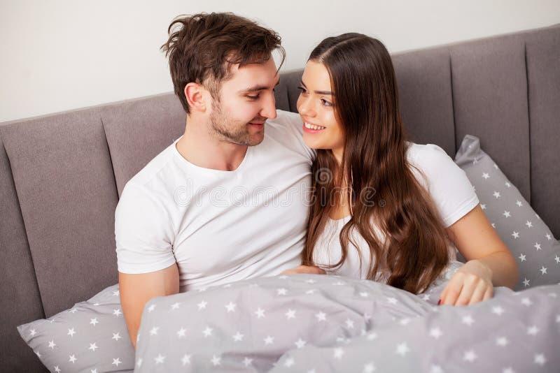 Счастливые пары имея потеху в кровати Интимные чувственные молодые пары в спальне наслаждаясь одином другого стоковое фото