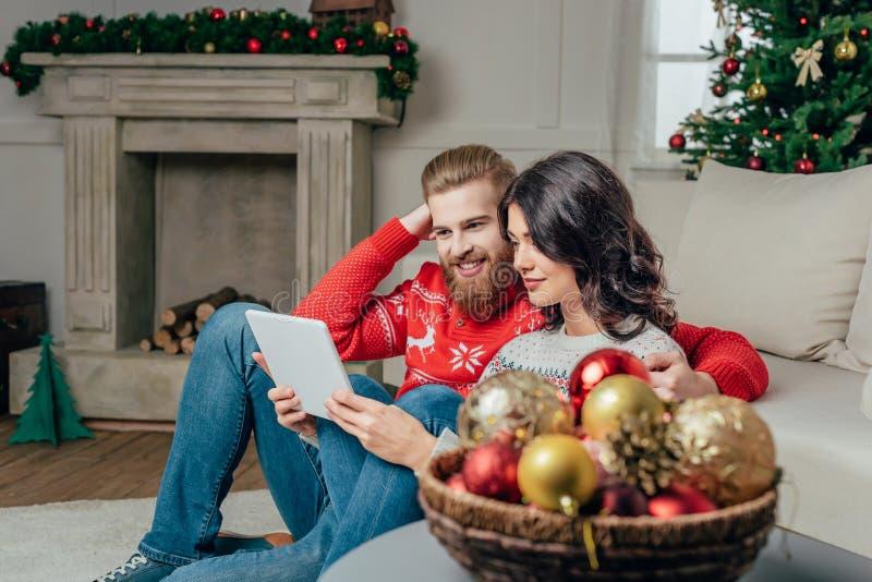 счастливые пары используя таблетку пока сидящ на поле в рождестве стоковая фотография rf