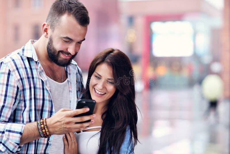 Счастливые пары используя smartphone в городе в дождливом дне стоковое фото