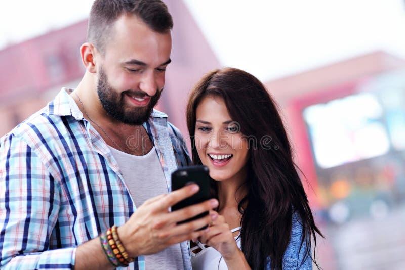 Счастливые пары используя smartphone в городе в дождливом дне стоковая фотография rf