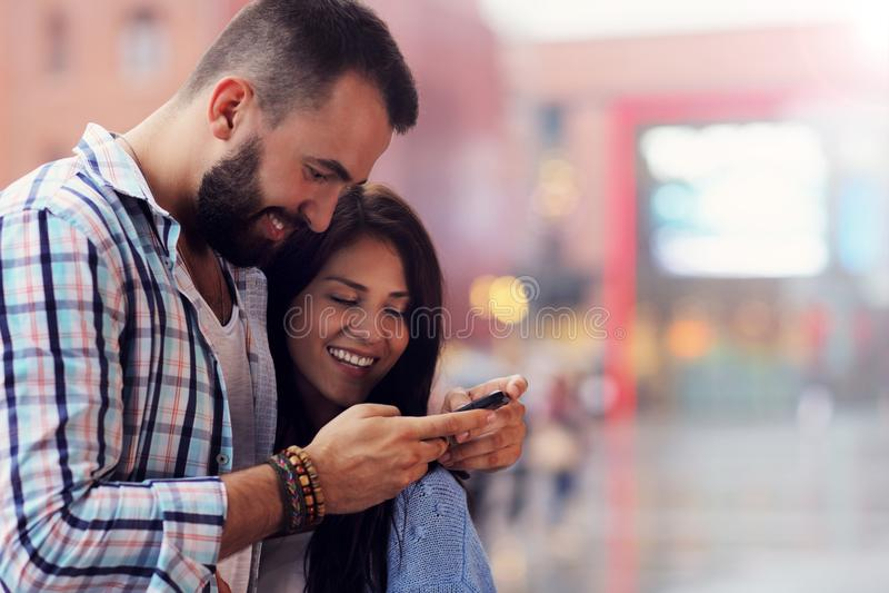 Счастливые пары используя smartphone в городе в дождливом дне стоковое изображение