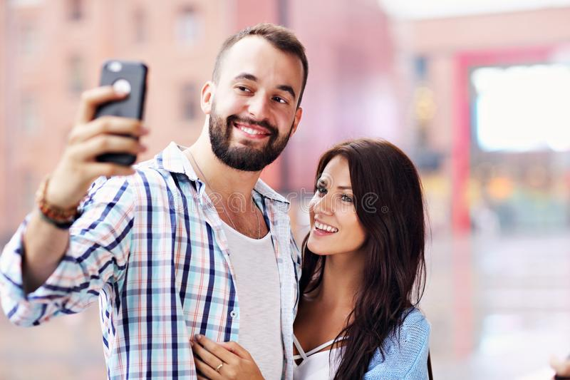 Счастливые пары используя smartphone в городе в дождливом дне стоковые изображения
