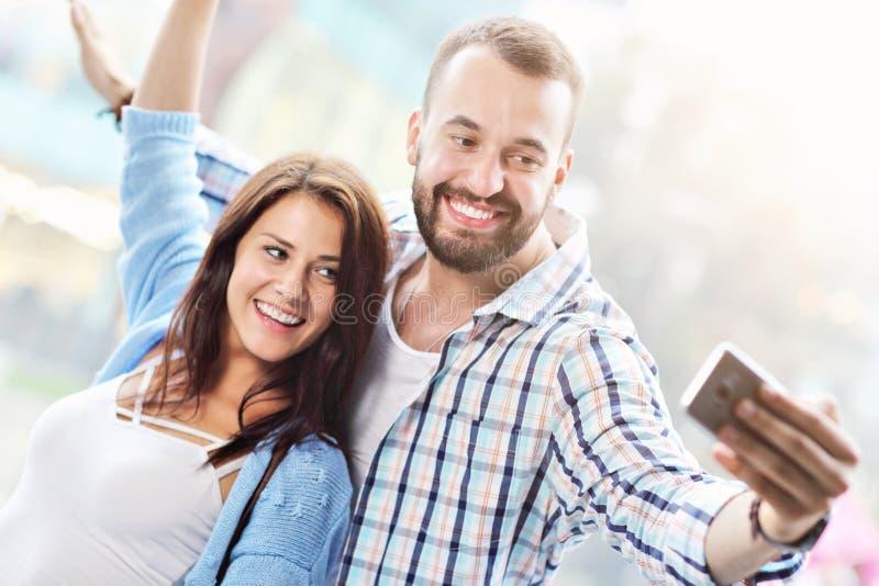 Счастливые пары используя smartphone в городе в дождливом дне стоковые изображения rf