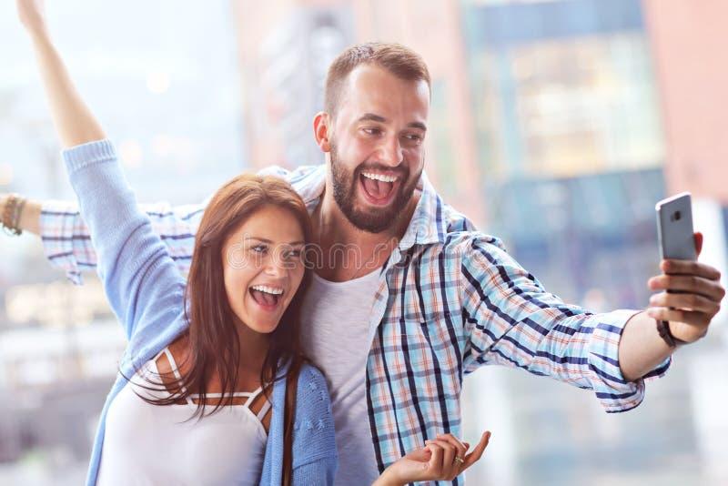 Счастливые пары используя smartphone в городе в дождливом дне стоковые фотографии rf