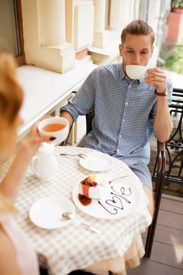 Счастливые пары наслаждаясь кофе на кофейне стоковое фото rf