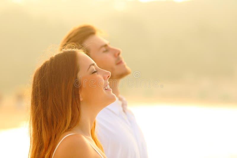 Счастливые пары на пляже дыша свежим воздухом на заходе солнца стоковая фотография rf