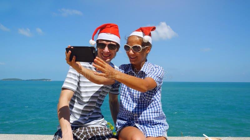 Счастливые пары носят шляпу ` s Санты делая selfie с smartphone на пляже празднуя рождество и Новый Год стоковые фотографии rf