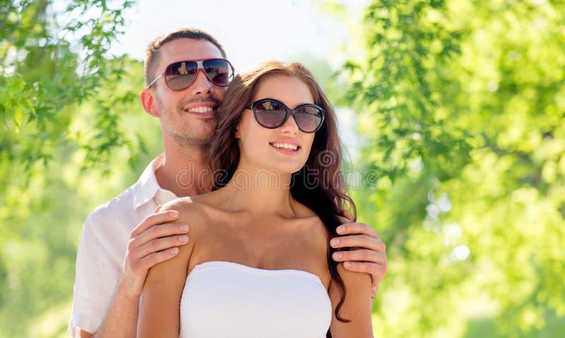 Счастливые пары обнимая над зеленой естественной предпосылкой стоковое изображение