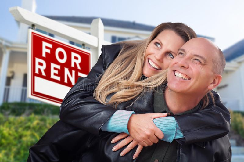 Счастливые пары обнимая перед для знаком и домом недвижимости ренты стоковое изображение rf