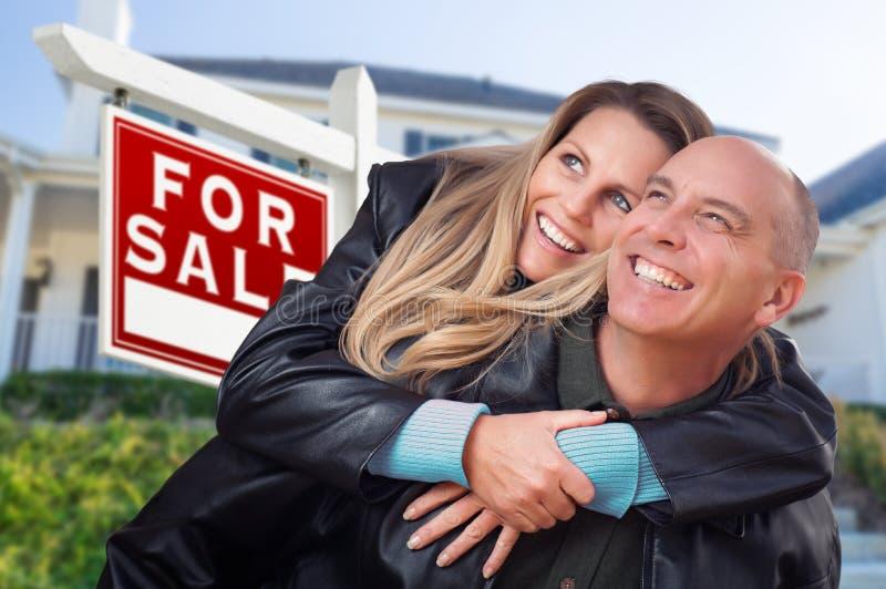 Счастливые пары обнимая перед для продажи знаком и домом недвижимости стоковое фото