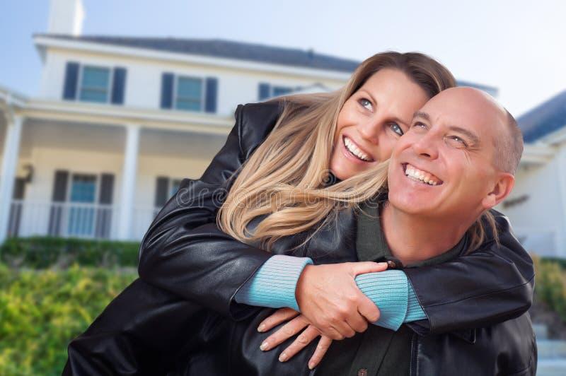 Счастливые пары обнимая перед красивым домом стоковые фото