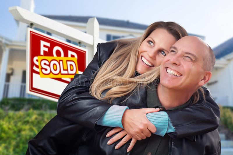 Счастливые пары обнимая перед проданными знаком и домом недвижимости стоковые фото