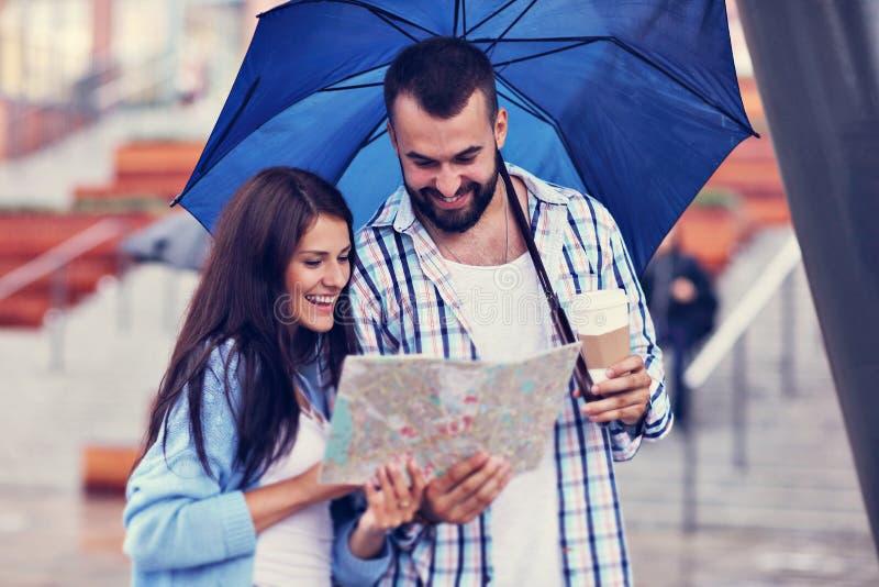 Счастливые пары под зонтиком в городе стоковое изображение