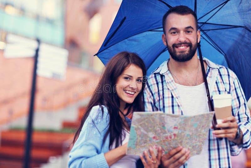 Счастливые пары под зонтиком в городе стоковое фото rf