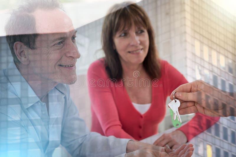 Счастливые пары получая ключи дома от риэлтора; множественная выдержка стоковые изображения rf