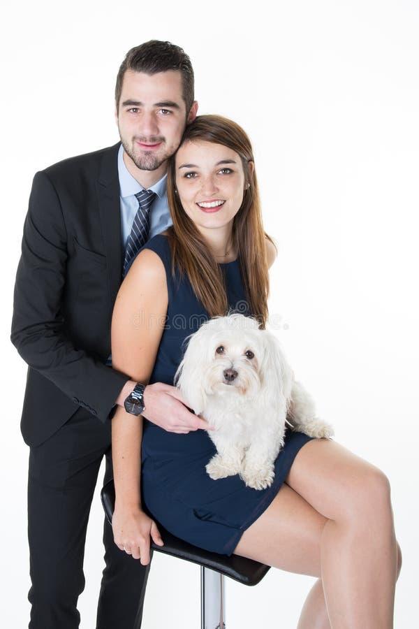 Счастливые пары при собака сидя над белой предпосылкой стоковые изображения
