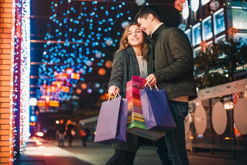 Счастливые пары при хозяйственные сумки наслаждаясь ночой на предпосылке города стоковые фотографии rf