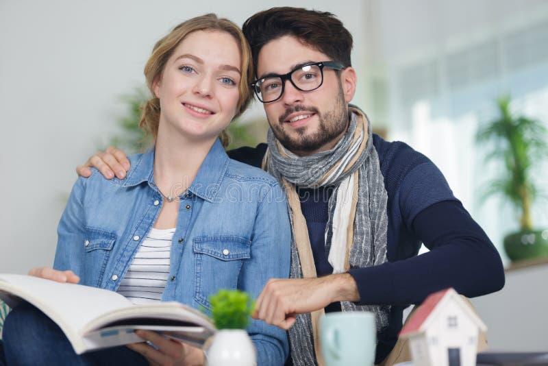 Счастливые пары рядом с миниатюрой дома стоковое изображение