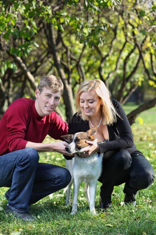 Счастливые пары сидят на корточках и касатьются собаке в парке стоковое фото rf