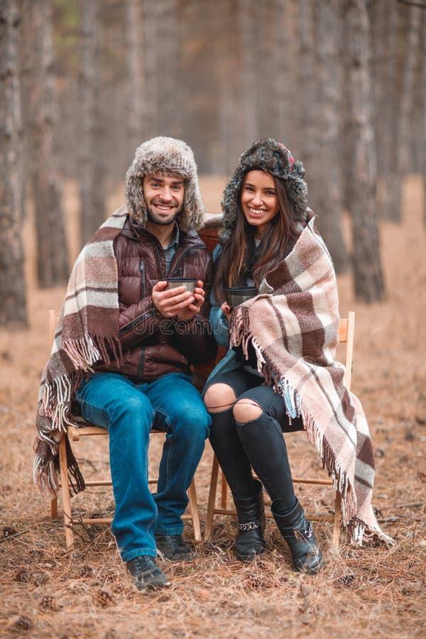 Счастливые пары сидя в лесе осени, выпивая горячем чае и усмехаться стоковая фотография