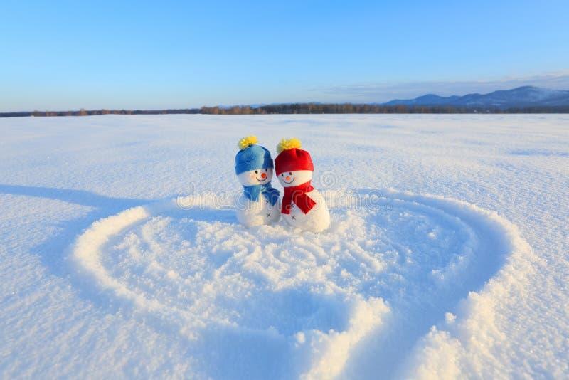 Счастливые пары снеговика в влюбленности стоя на снеге Покрашенное сердце Сочинительства 2019 Ландшафт с горами стоковые изображения