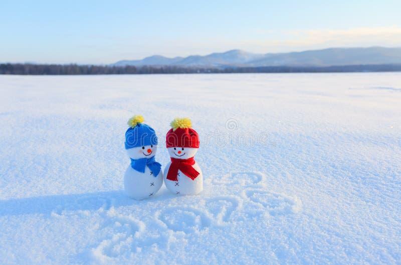 Счастливые пары снеговика в влюбленности стоя на снеге Сочинительства 2019 Ландшафт с горами в холодном зимнем дне стоковое изображение
