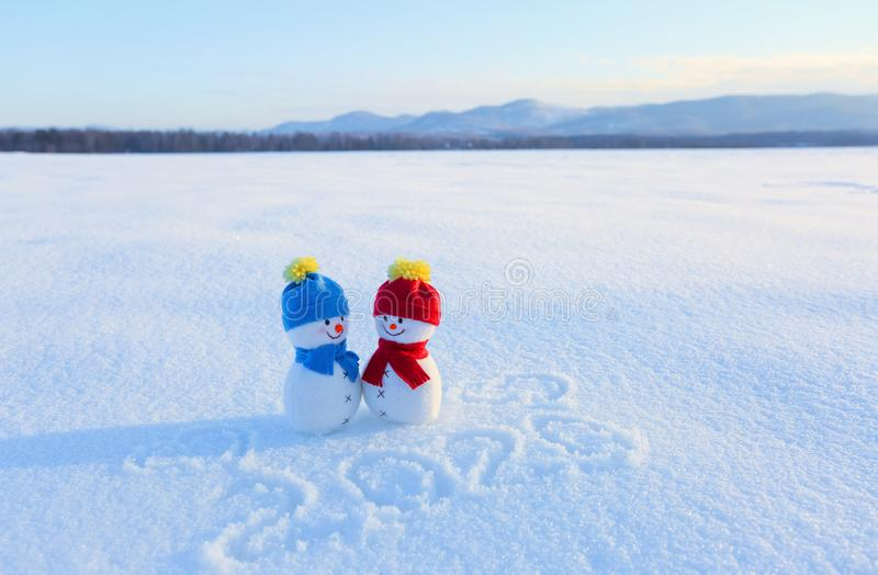 Счастливые пары снеговика в влюбленности стоя на снеге Шляпа и шарф голубого красного цвета Сочинительства 2019 Ландшафт с горами стоковое фото
