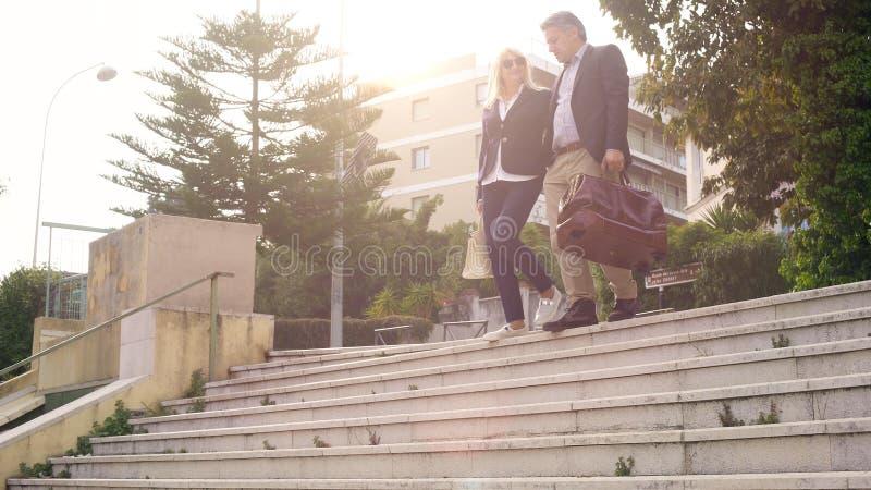 Счастливые пары с сумками покидая гостиница и идя вниз, перемещение каникул стоковые изображения rf