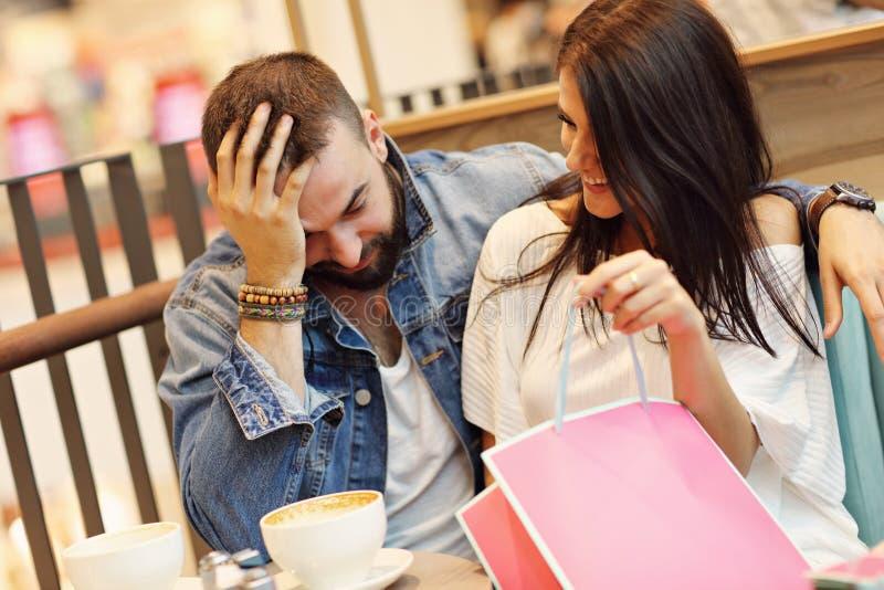 Счастливые пары с хозяйственными сумками в кафе стоковая фотография