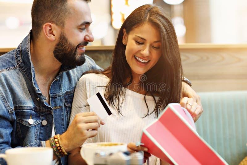 Счастливые пары с хозяйственными сумками в кафе стоковые фото