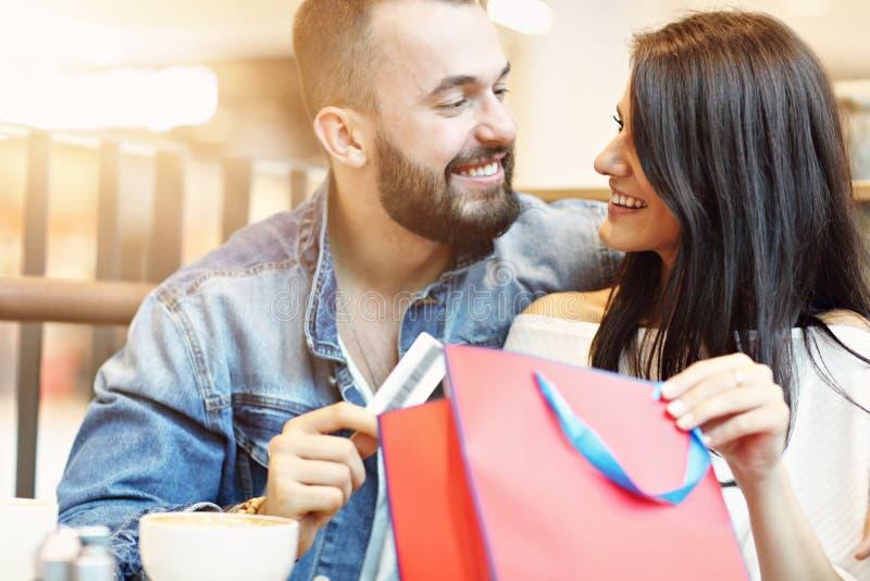 Счастливые пары с хозяйственными сумками в кафе стоковая фотография rf