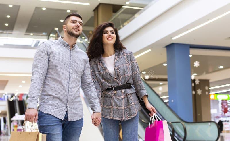 Счастливые пары с хозяйственными сумками идя в торговый центр стоковые изображения