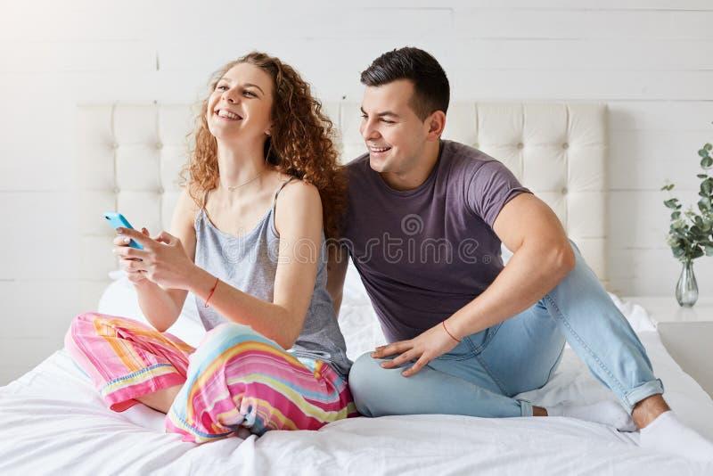Счастливые пары тратят утреннее время в спальне, проверяющ социальную стоковая фотография rf