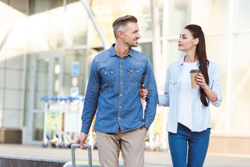 счастливые пары туристов пересекая пешеходные, держа руки и стоковое изображение rf