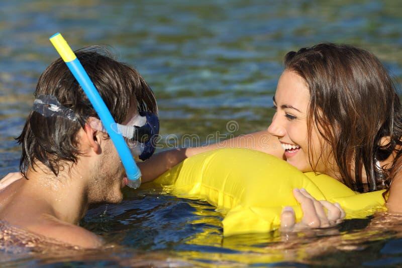 Счастливые пары туристов шутя купая на пляже стоковое изображение rf