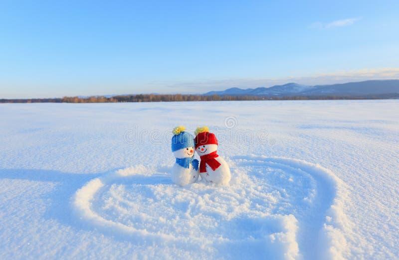Счастливые пары усмехаясь снеговика Шляпа и шарф голубого красного цвета Покрашенное сердце и 2019 на снеге Счастливый день ` s в стоковая фотография