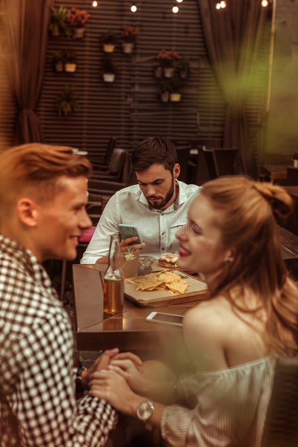 Счастливые пары flirting пока их друг нажимает на телефоне стоковое фото